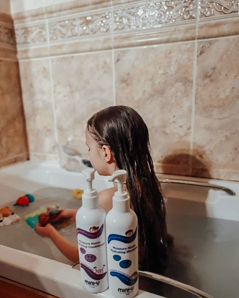 Child in bath with wet hair, mini-u shampoo and conditioner in forefront