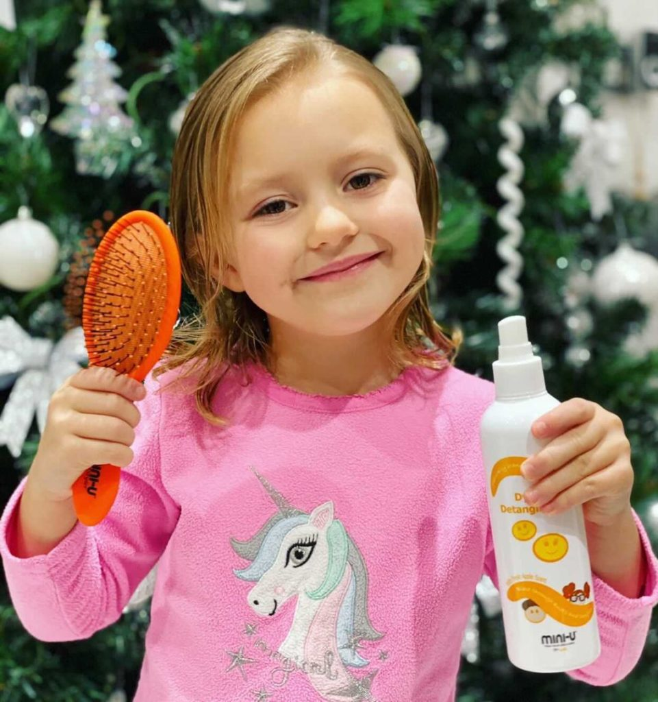 Image of young girl holding pro styler brush and dynamite detangling spray